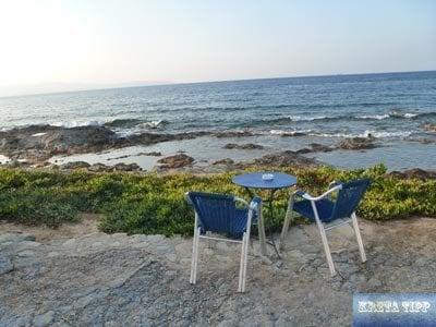 Stühle und Tisch einer Taverne direkt am Meer auf Kreta
